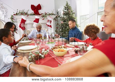 Family With Grandparents Saying Grace Before Christmas Meal poster