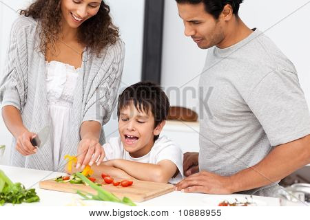 Happy Family Preparing A Salad Together In The Kitchen