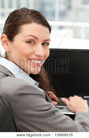 Rear View Of A Happy Businesswoman Working On Her Laptop