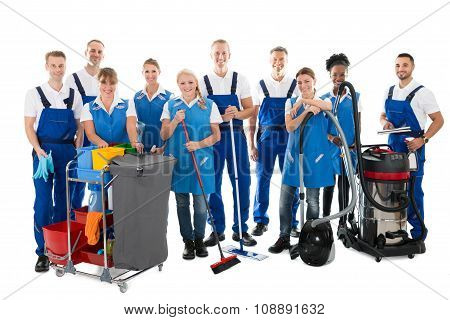 Portrait Of Happy Janitors With Cleaning Equipment