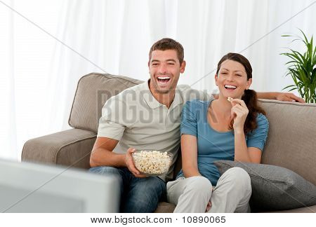 Lovely Couple Laughing While Relaxing In Front Of The Television