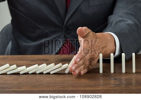 Businessman Stopping Dominoes Falling On Wooden Desk