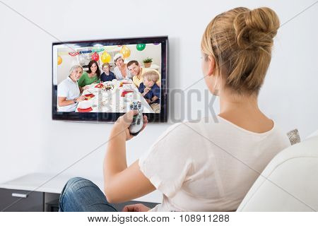Young Woman Watching Television While Sitting On Sofa