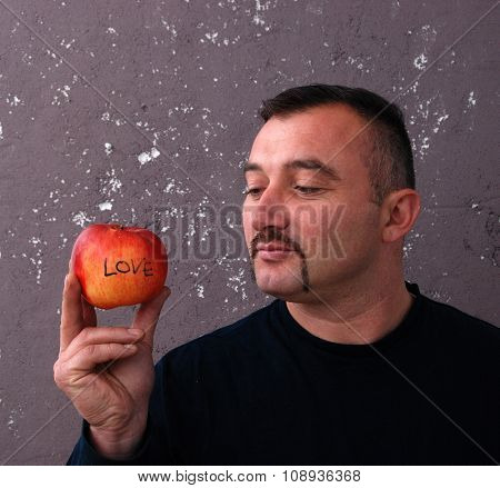 Man With Mustaches looking on an apple
