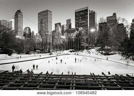 Central Park Winter Scene and Skyscrapers in Black & White. Ice skating on the Wollman Rink in wintertime, Central Park, Manhattan, New York City. poster