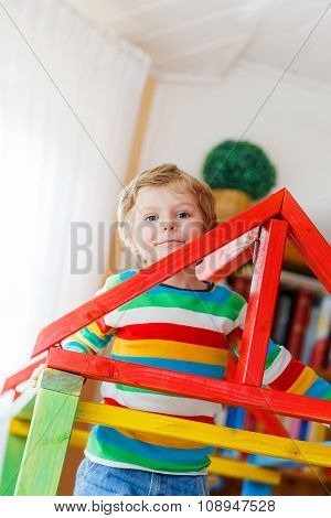 Little blond kid boy playing in selfmade wooden colorful house