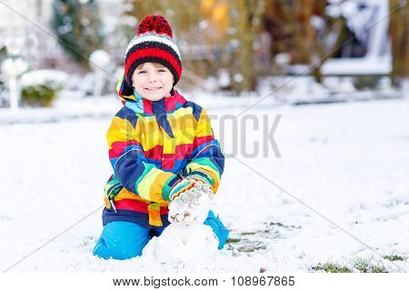 Beautiful kid boy in colorful clothes making a snowman