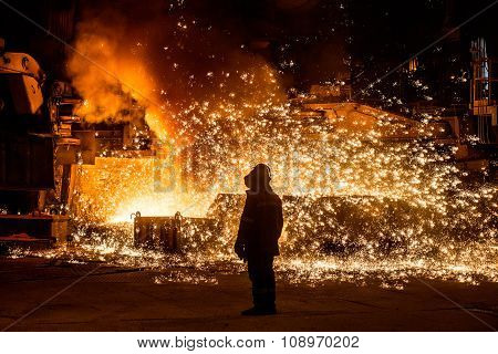 Steelworker near a blast furnace with sparks.