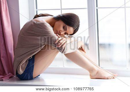 Young woman sitting near window