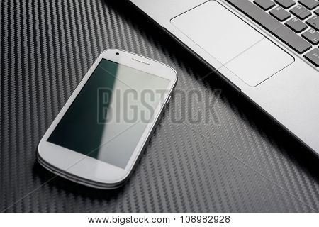 Blank Business Mobile With Green Reflection Lying In Front Of A Keyboard, All Above A Carbon Layer
