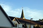 The steeple of the Holy Childhood of Jesus Roman Catholic Church towers over the roof of the Holy Childhood Community Center in Harbor Springs, Michigan. poster