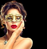 Beauty model woman wearing venetian masquerade carnival mask at party isolated on black background. Christmas and New Year celebration. Glamour lady with perfect make up and hairstyle poster