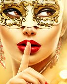 Beauty model woman wearing venetian masquerade carnival mask at party over holiday glowing gold background. Christmas and New Year celebration. Glamour lady with perfect make up and jewellery poster