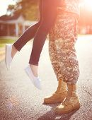 Young military couple kissing each other homecoming concept warm orange toning applied poster