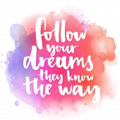 Follow your dreams, they know the way. Inspirational quote about life and love.  Modern calligraphy text, handwritten with brush on pink and orange watercolor splash background with bokehs. poster