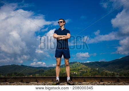 Young attractive man in sunglasses stands against the blue sky with arms folded