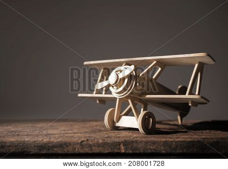 wood toy airplane on wood table with blue clean background.