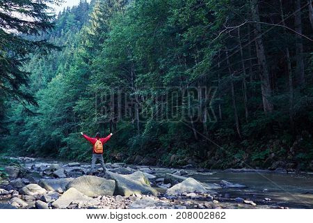 Rear view of male hiker with outstretched hands hiking on mountain river