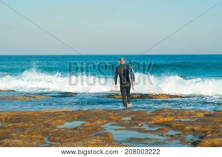 Professional surfer carrying his surfboard while going to the sea professional surfer in black diving suits ready to surf walk to the ocean.