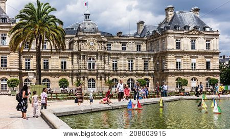 Paris France - Jule 11 2017: Children with parents launch a toy colorful boats in a pond near Luxembourg Palace in the Luxembourg Gardens (Jardin du Luxembourg) one of the most beautiful gardens in Paris.