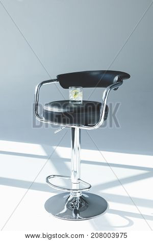 Gin Tonic cocktail in glass on bar stool in studio