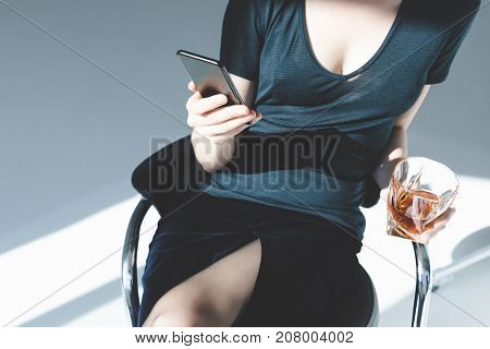 Woman With Smartphone And Glass Of Whisky