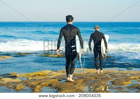 Professional surfers carrying their surfboards while going to the sea professional surfers in black diving suits ready to surf walk to the ocean.