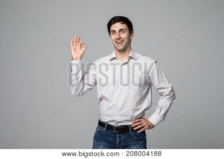 Happy Okay Man. Young Handsome Man In Casual Shirt Gesturing Okay And Smiling At Camera Against Grey