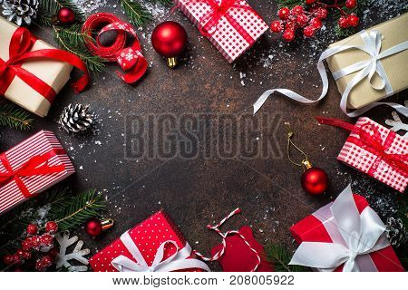 Christmas background or greeting card. Christmas presents in red and white box on dark stone table with festive decorations. Top view with copy space.