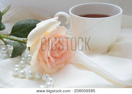 rendezvous,  Cup of tea and a flower delicate roses on the table next to exquisite beads, a still life full of bright thoughts and happiness