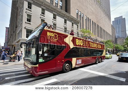 NEW YORK CITY USA - AUG. 28 : City tour bus on street in Manhattan on August 28 2017 in New York City NY. Manhattan is the most densely populated borough of New York City.
