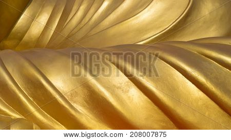 Gold yellow detail metal of carved Buddha statues abstract background texture.