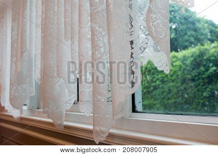 Luxury white curtain drapes at window morning in a home.