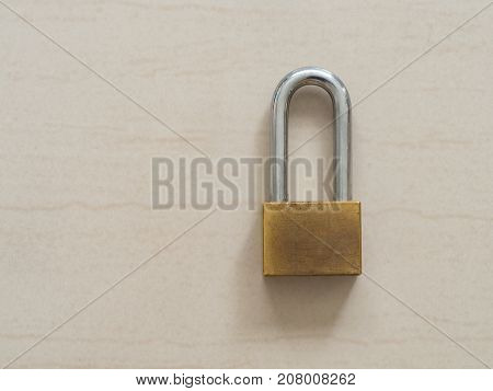 Gold padlock locked on floor. Concept of secure and safety lock.