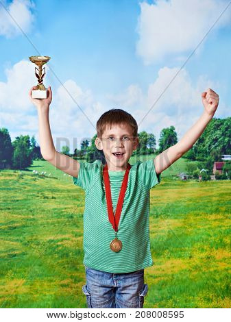 Happy Boy Winner With Cup And Medal On Nature