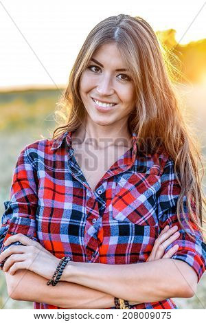 Beautiful girl field. Summer in nature. Corrects long hair. In a shirt and shorts. A sunny day woman brunette, close-up portrait. Tenderness, dreaming, fantasizing.