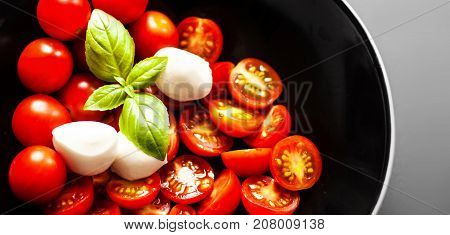 Food ingredients - Tomatoes basil leaf mozarella cheese and black olives in a black bowl with copy space. Fresh vegetables and herbs over dark chalk board background. Healthy food diet nutrition concept.