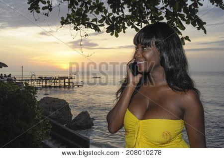 young attractive and glamorous African American black woman in chic and elegant summer dress talking on mobile phone at sunset beach in communication and networking concept