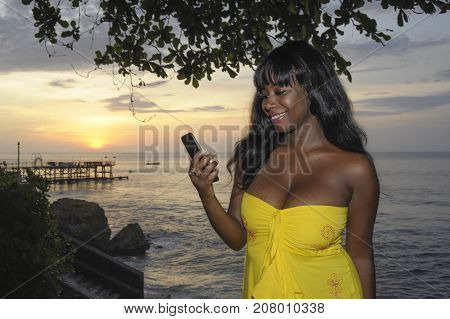 young attractive and glamorous African American black woman in chic and elegant summer dress using internet texting on mobile phone at sunset beach in communication and networking concept