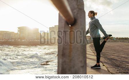 Female Runner Stretching By Seaside Promenade