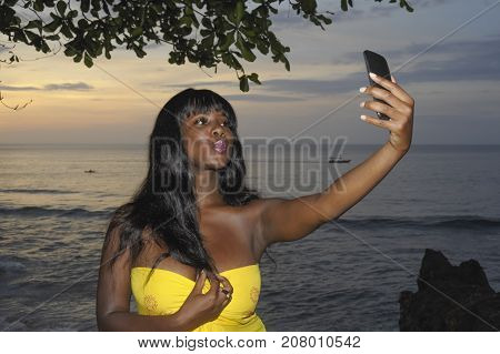 young attractive and glamorous African American black woman in chic summer dress taking selfie picture or video on mobile phone at sunset beach in holiday trip social media update concept