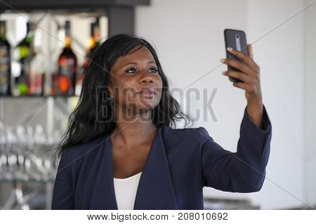 young attractive and happy black afro american woman in casual elegant clothes taking selfie portrait photo with mobile phone camera smiling cheerful and positive sitting at restaurant bar