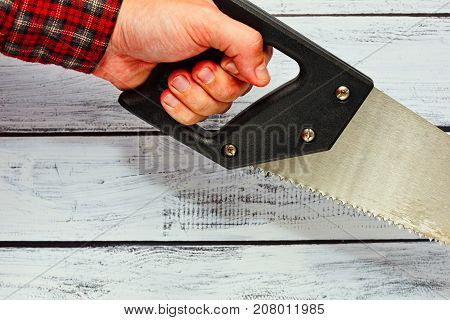Male Person Holding A Hand Saw
