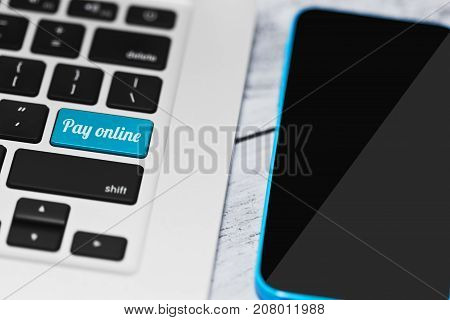 Laptop keyboard with online payment conceptual tagline on enter key and a smartphone nearby. Purchasing via internet without leaving home idea. Online banking or retail concept. Selective focus.