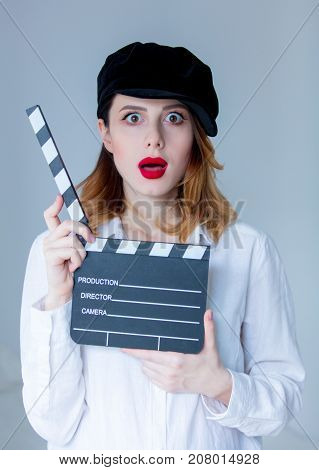 Young Surprised Redhead Woman In Hat Holding Movie Clapboard