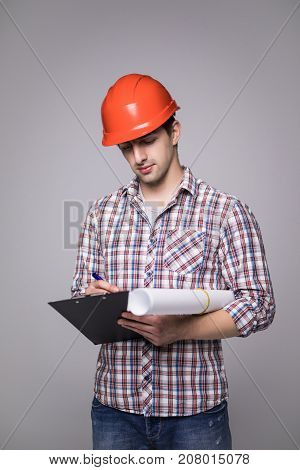 Handsome Man In A Black Suit And Construction Helmet Looking To The Side And Holding Black Folder On