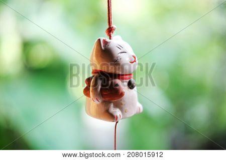 Maneki Neko is Japanese lucky cat doll hanging on the window