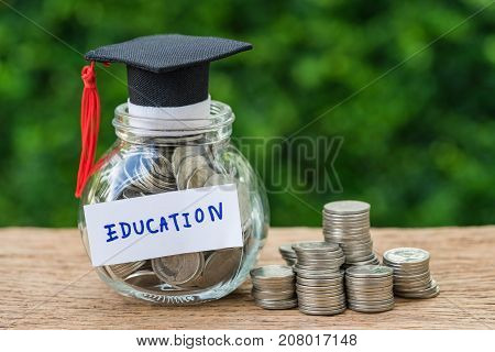 glass jar with full of coins and graduates hat label as Education education and stack of coins or savings concept.