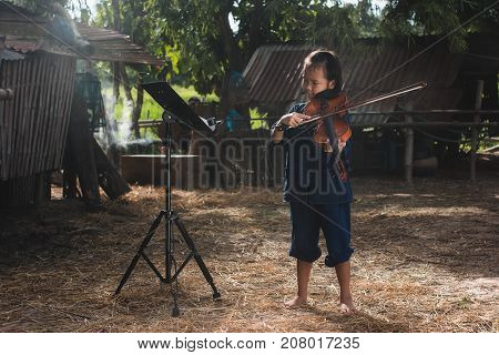 Rural children playing violin with fraind at countrysidePlaying music is the relaxation of rural children in Asia.