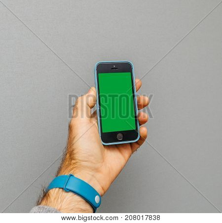 PARIS FRANCE - OCT 4 2017; Man holding iPhone 5 SE smartphone against grey background in blue leather protection cover with green chroma key
